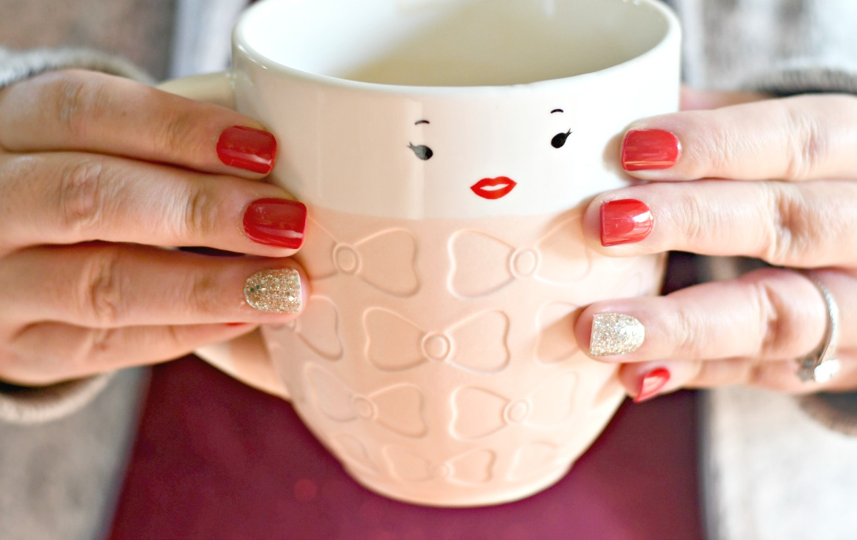 holding a coffee cup with red Impress Nails on