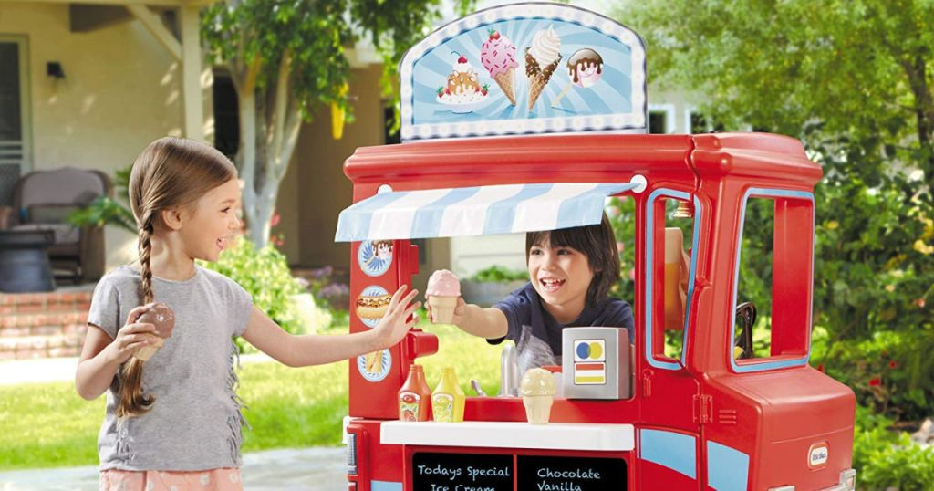 boy and girl playing in little tikes 2-in-1 food truck outside
