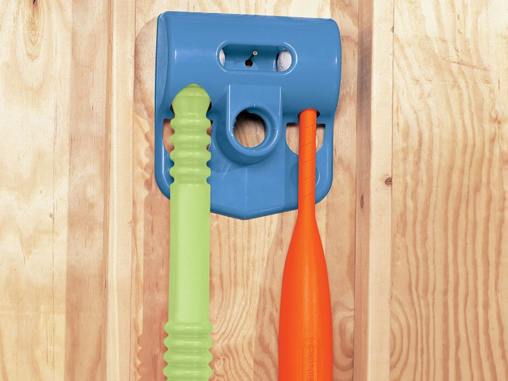 blue, green, and orange Little Tikes TotSports T-Ball Set hanging on wooden wall