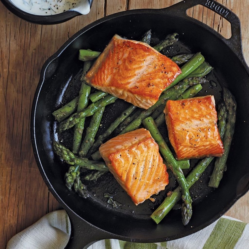 lodge cast iron skillet with salmon and asparagus in the pan