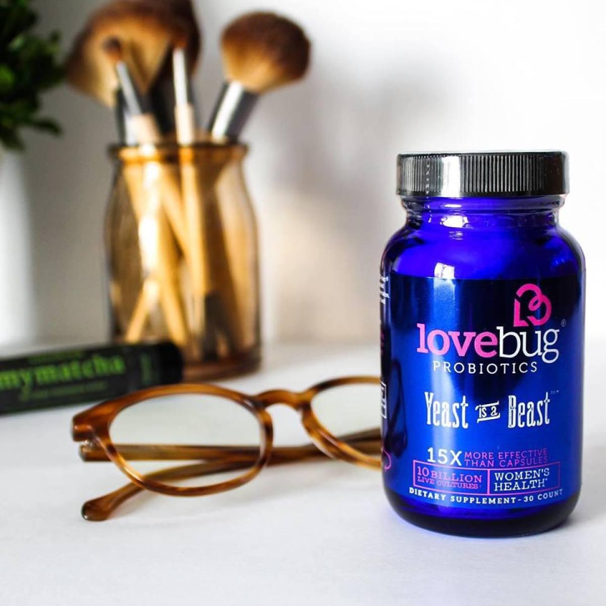 LoveBug probiotics on a counter by a pair of glasses and cosmetic brushes