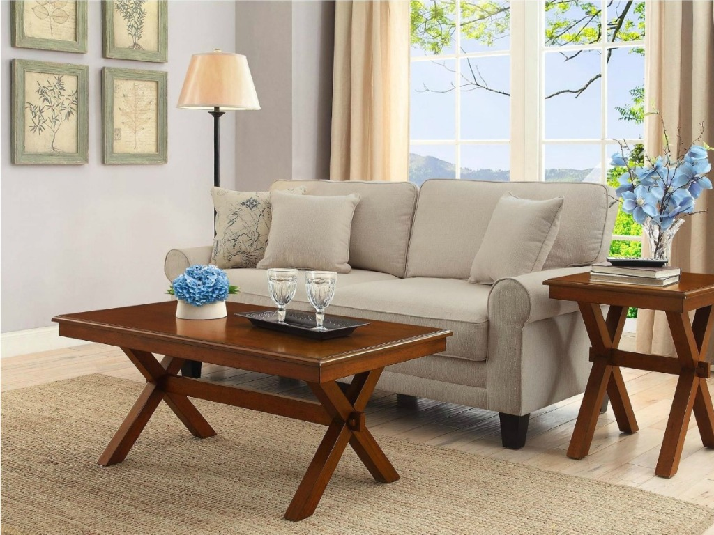 Maddox wooden coffee table with criss cross legs in front of couch