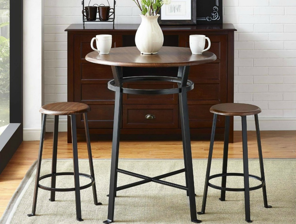 wood and metal pub dining set with vase of flowers and white mugs on top