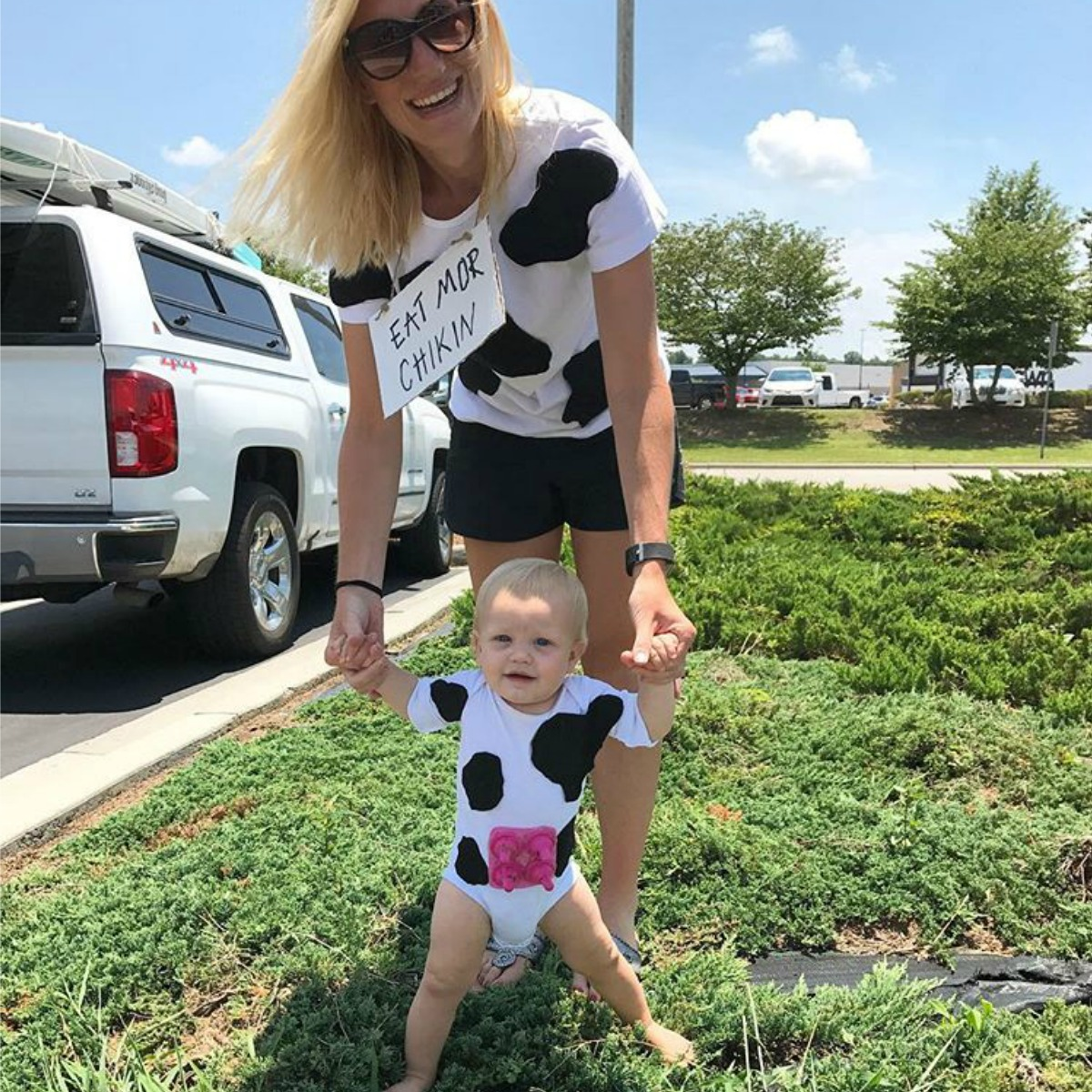 Mom and baby dressed as cows with white shirts covered in black felt spots