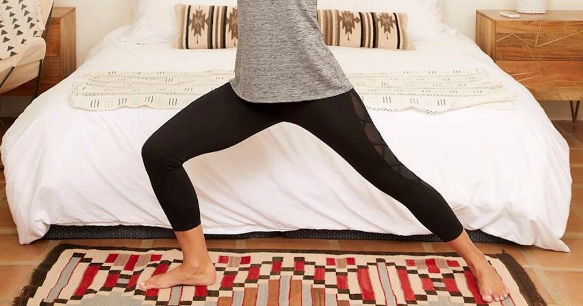 woman doing yoga wearing grey tank top and black leggings in front of bed