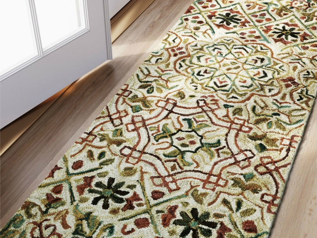 brown, green and cream-colored oriental runner rug in hallway