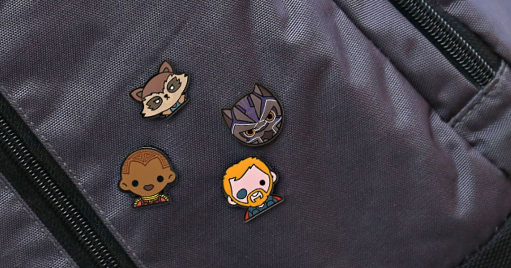 4 marvel character pins placed on a grey backpack