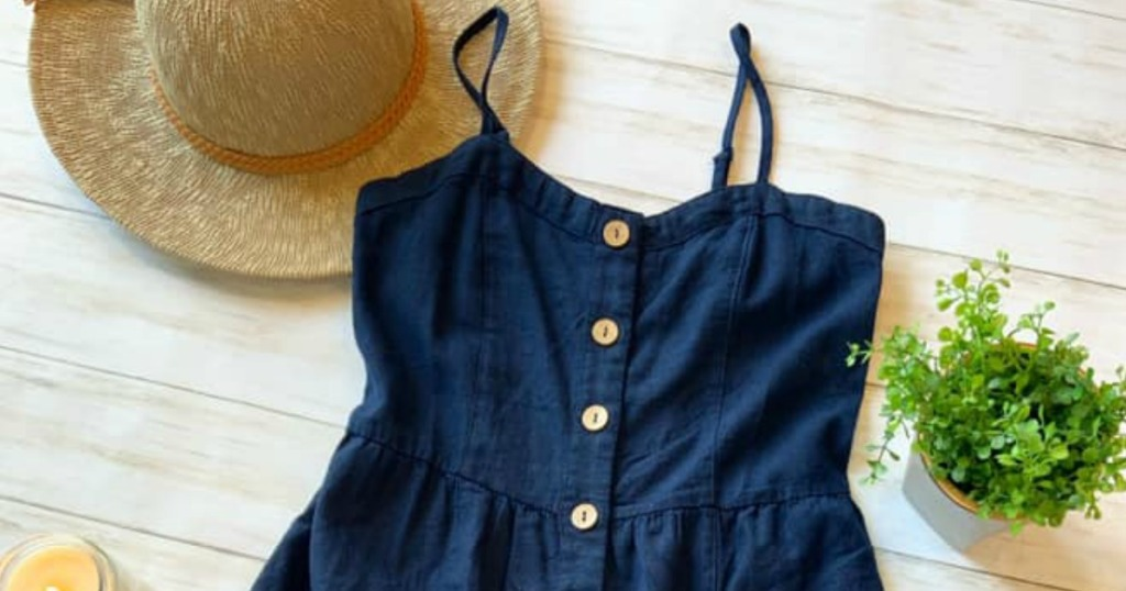 blue button-down dress with sun hat and plant