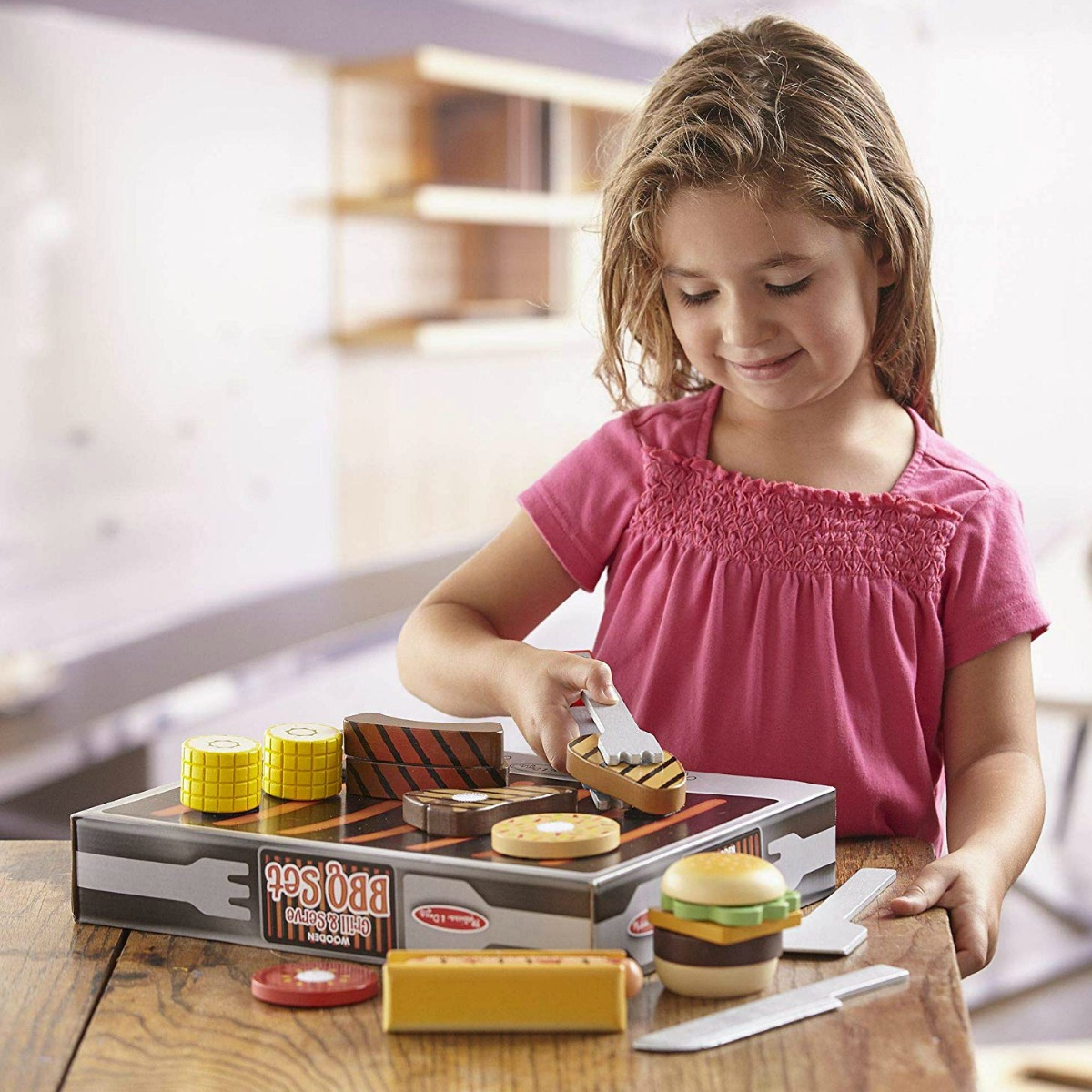 little girl playing with a Melissa & Doug BBQ set at a table