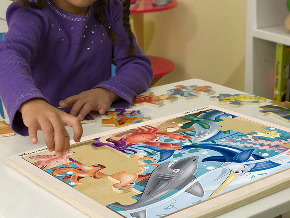 little girl doing a Melissa & Doug sea creature puzzle at a table