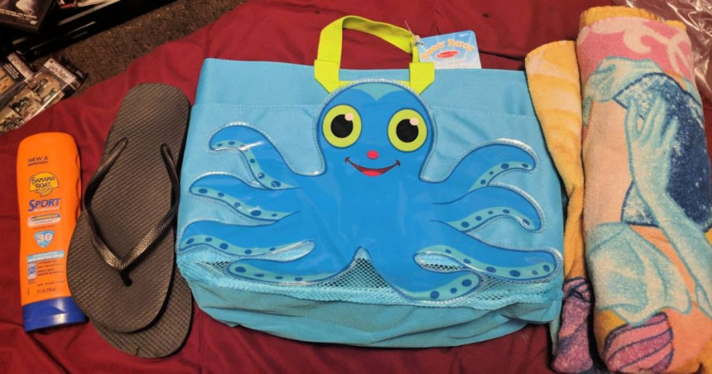 Melissa & Doug Sunny Patch Flex Octopus Large Beach Tote Bag With Mesh Panels on bed next to black sandals, sun screen, and towel