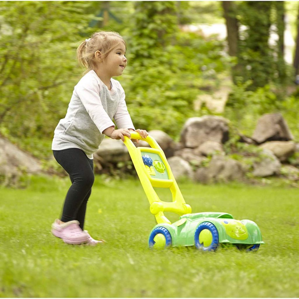 girl pushing Melissa & Doug Sunny Patch Snappy Turtle Mower in grass