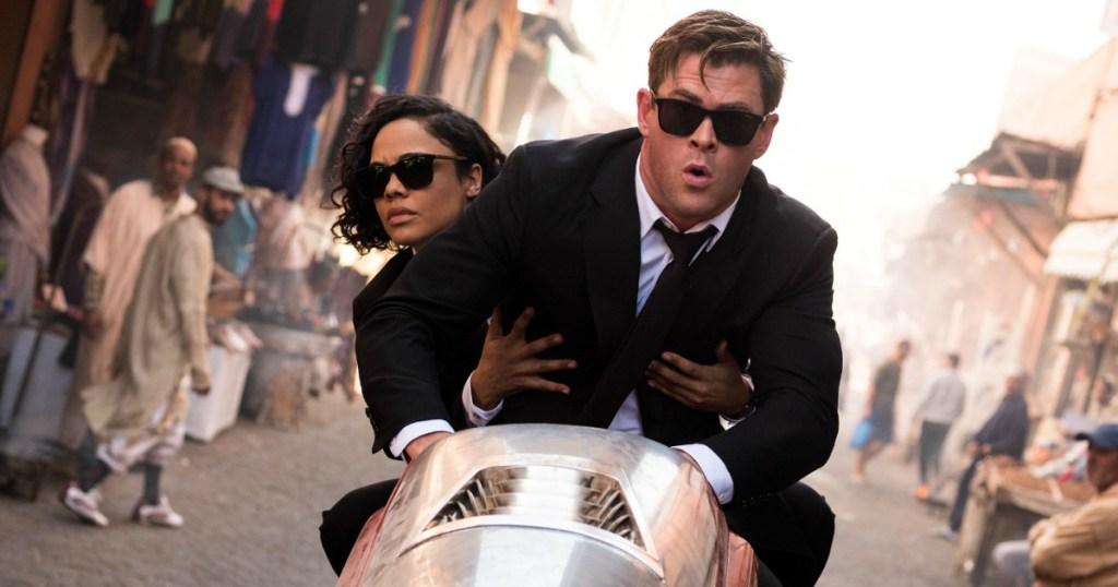 Chris Hemsworth and Tessa Thompson riding a motorcycle through a street market