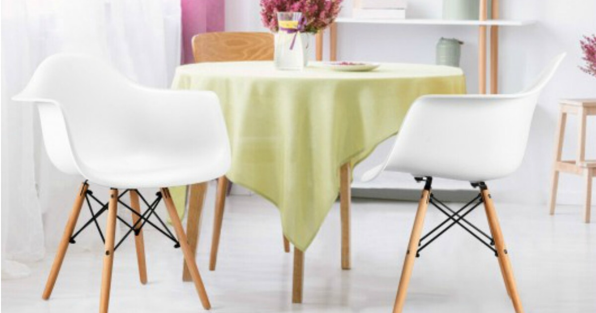 two white mid-century modern chairs with wooden legs, placed around a table