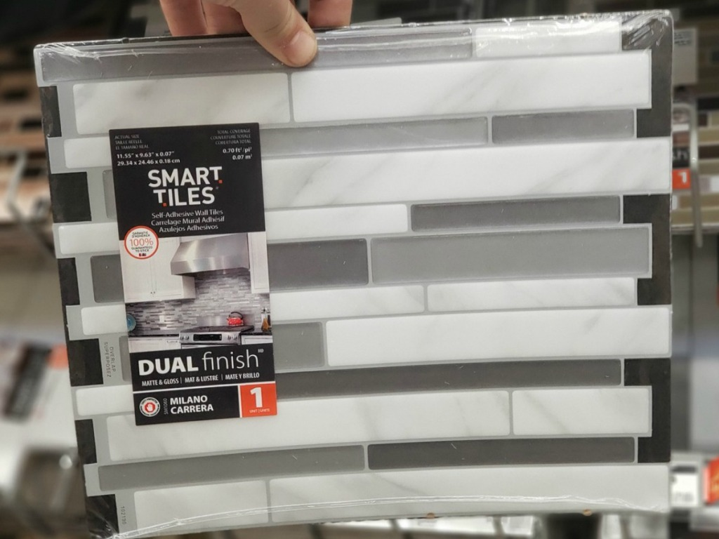 hand holding tile with white and grey by store display