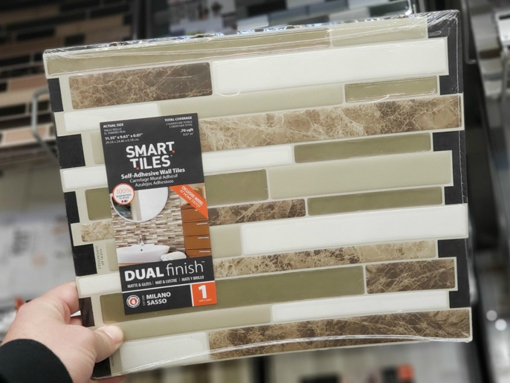 hand holding tile with beige and white at store display