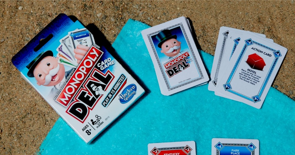 Monopoly Deal card game box on counter top with several cards revealed