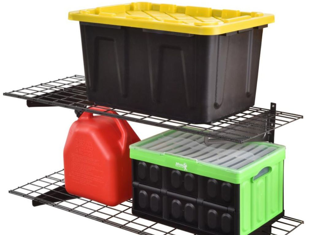 two muscle racks on top of each other with black tote with yellow lid, gas can, and black and green box