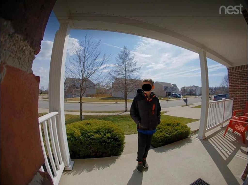 nest doorbell view of kid standing on front porch in neighborhood