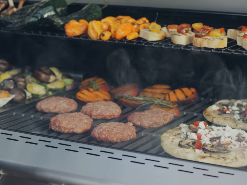 Burgers, pizza, and veggies being grilled on large Nexgrill Deluxe grill