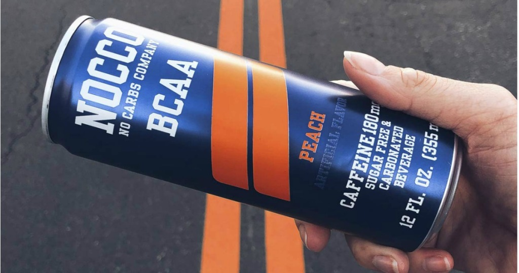 Nocco peach drink held over road stripes