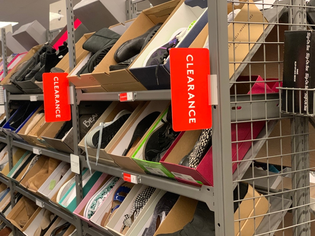 shoes in boxes on shoe rack with clearance signs
