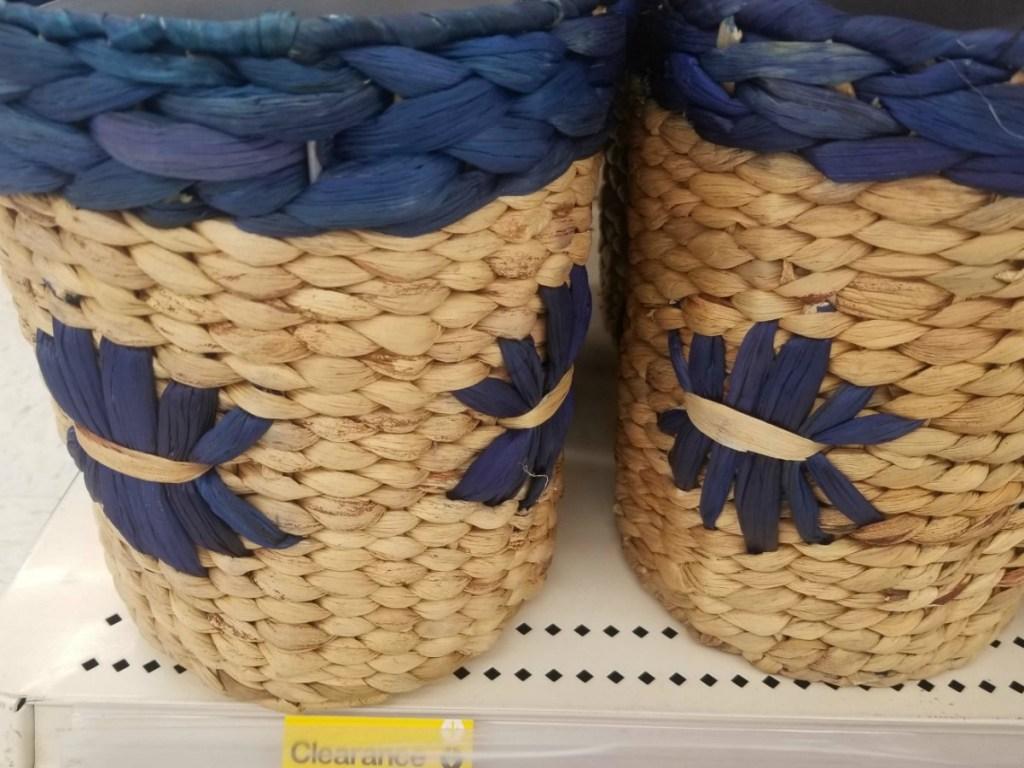 2 wicker blue and tan waste baskets on store shelf