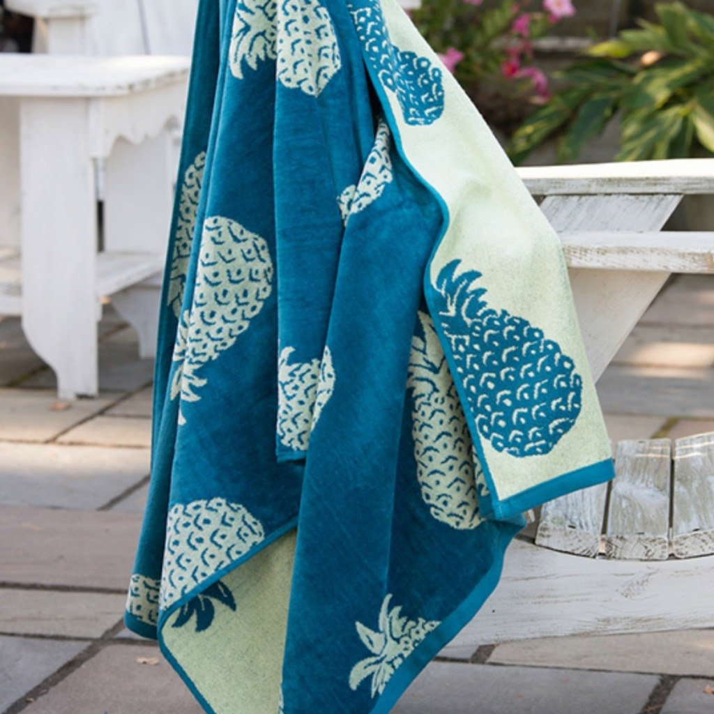 mint and teal pineapple oversized beach towels hanging on a bench