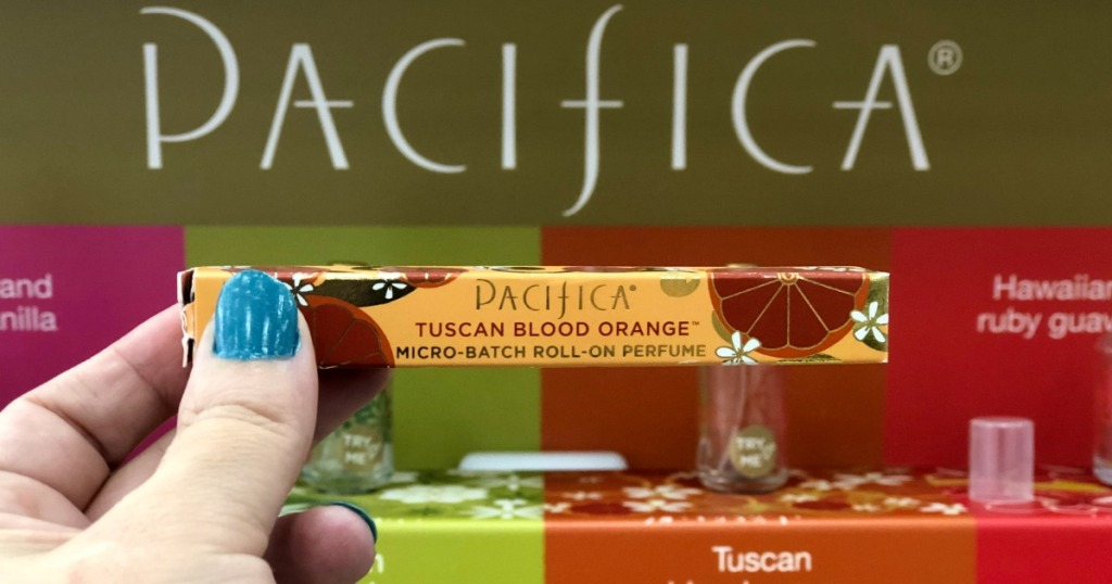 hand holding pacifica tuscan blood orange roll on perfume in front of pacifica sign