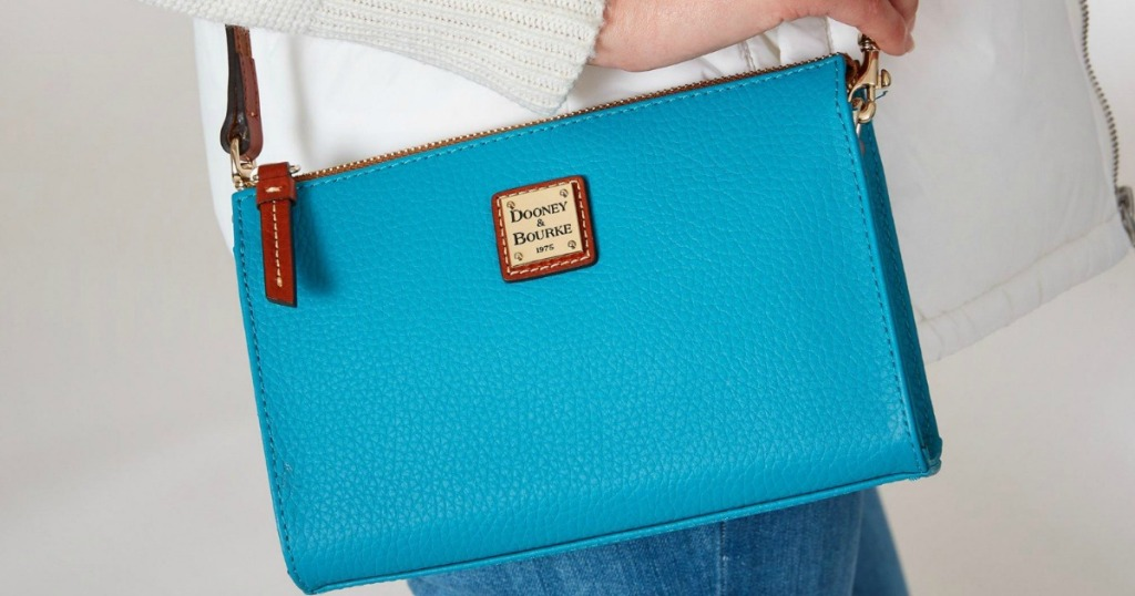 woman carrying dooney & bourke blue pebbled crossbody bag