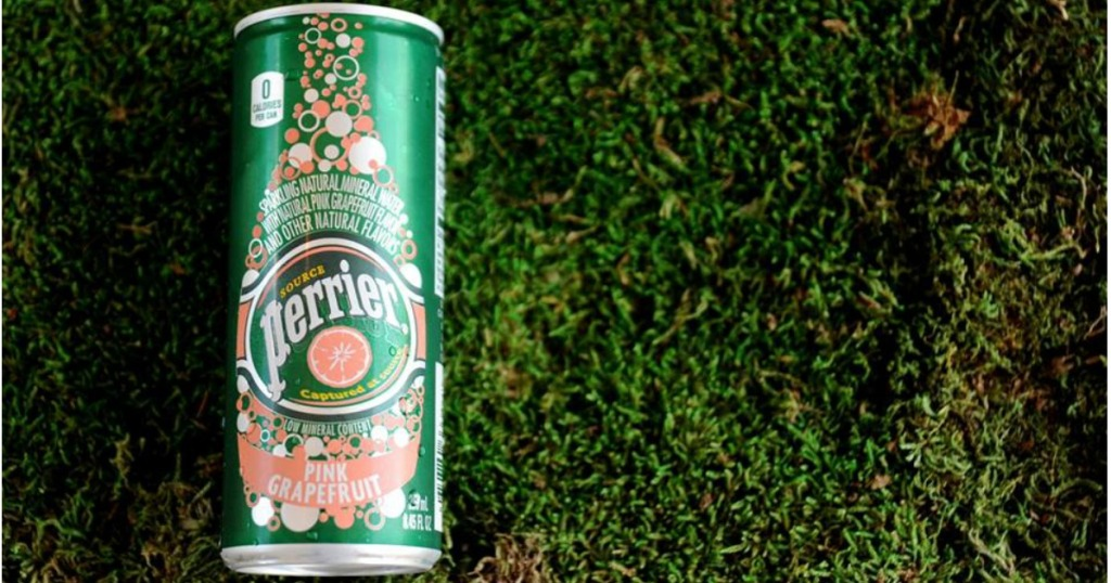 Can of Pink Grapefruit Perrier Flavored Mineral Water laying on grass