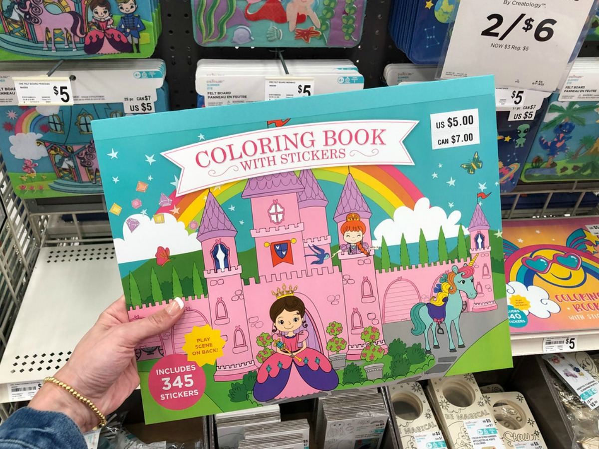 person holding a Creatology coloring book with stickers at Michaels