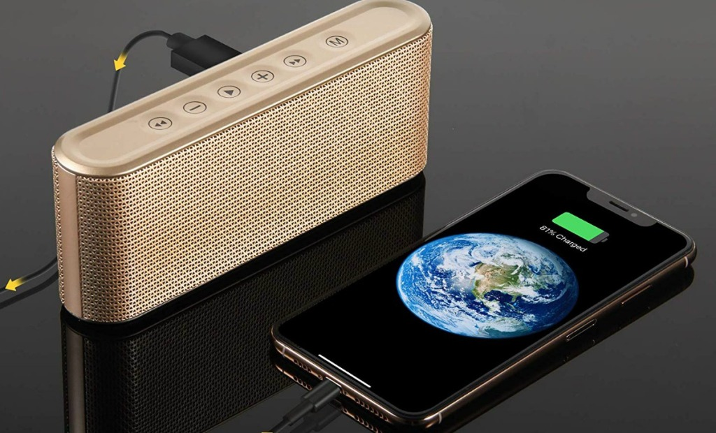 Gold slim bluetooth speaker sitting next to smart phone