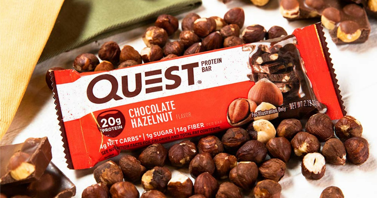 quest protein bar in package laying on top of hazelnuts