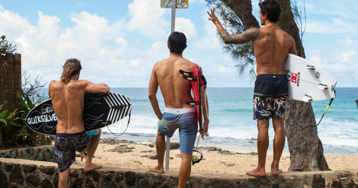 3 guys in boardshorts in front of ocean holding surf boards
