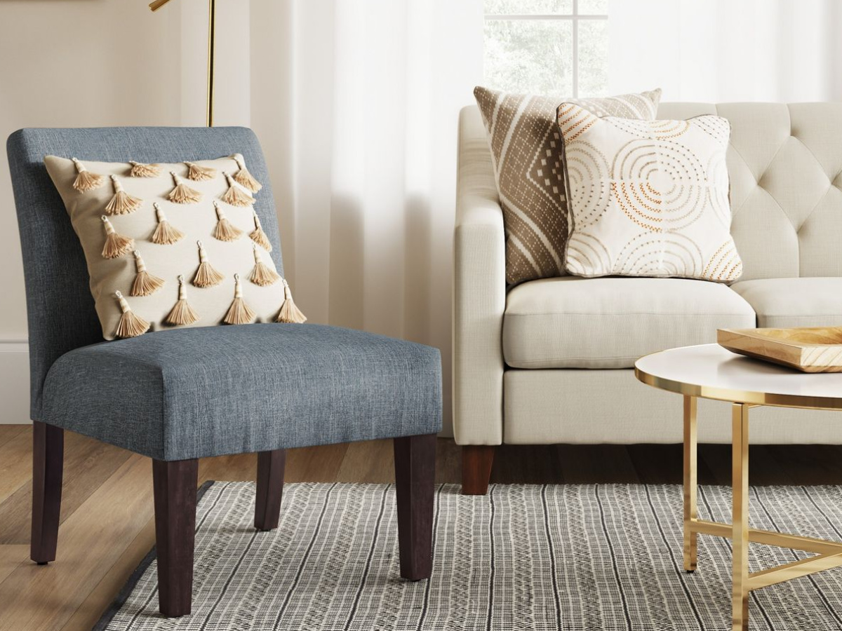 blue fabric and wood chair with throw pillow, next to a couch with pillows