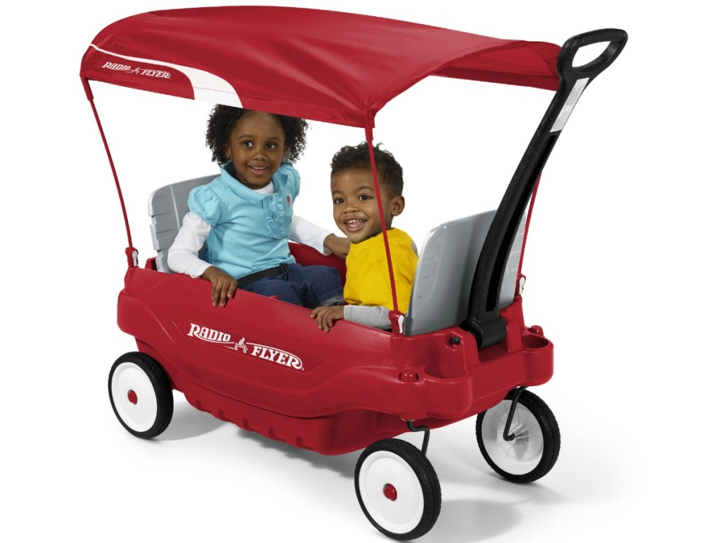 boy and girl sitting in radio flyer wagon with canopy top