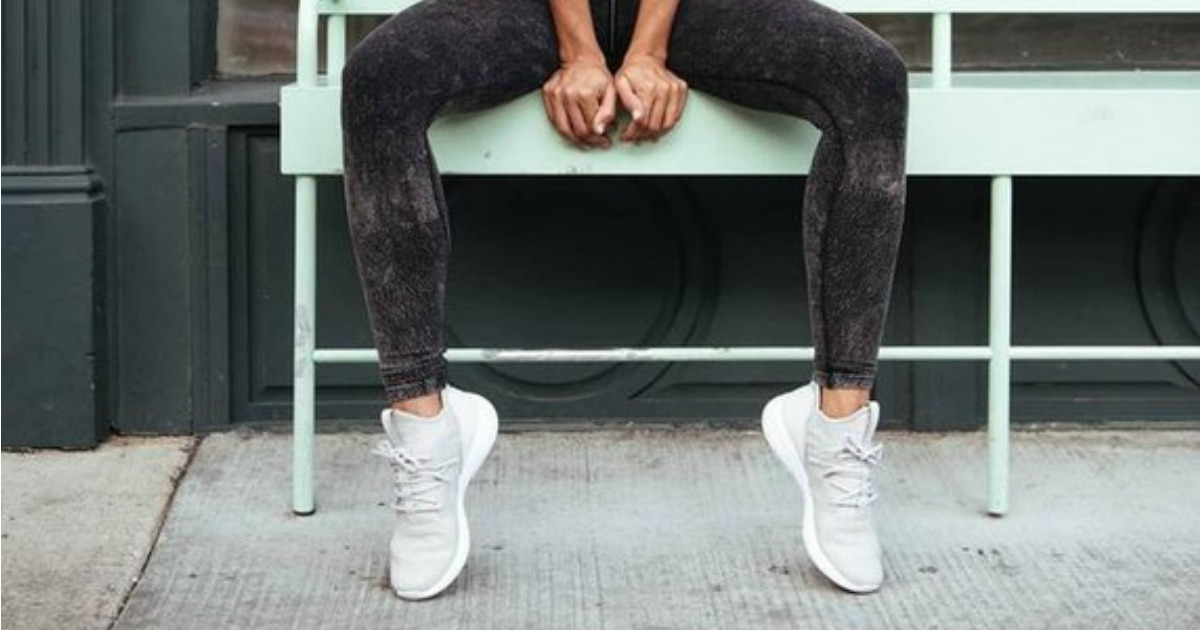 woman sitting on bench in athletic pose wearing Reebok shoes
