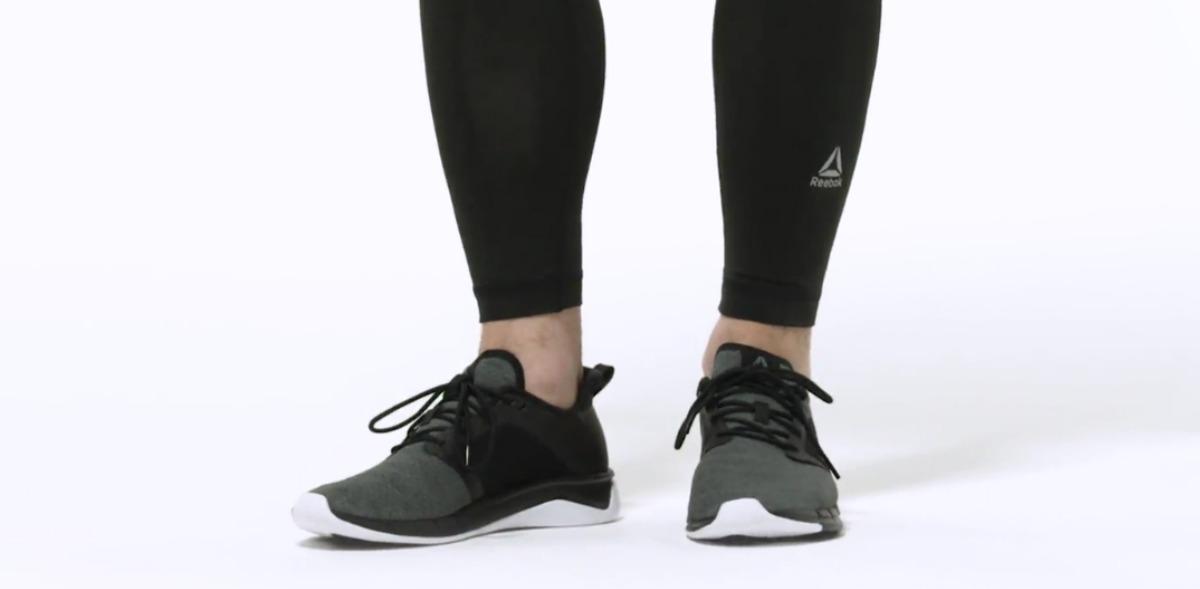 Man wearing gray and black Reebok running shoes