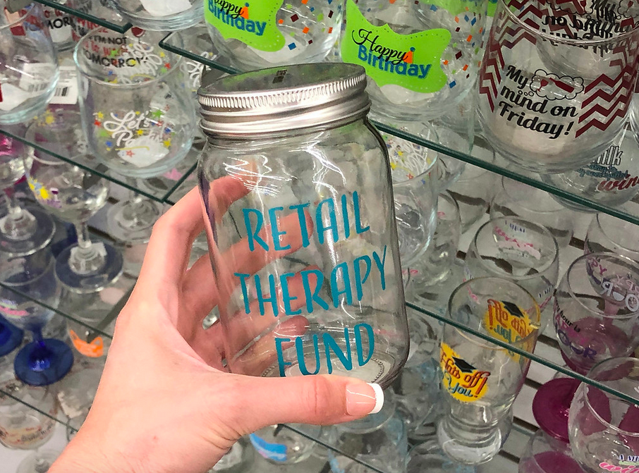 Woman holding Retail Therapy Fund Mason Jar inside Dollar Tree store