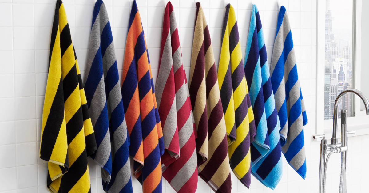 striped rugby towel sets hanging on hooks in a line on the wall