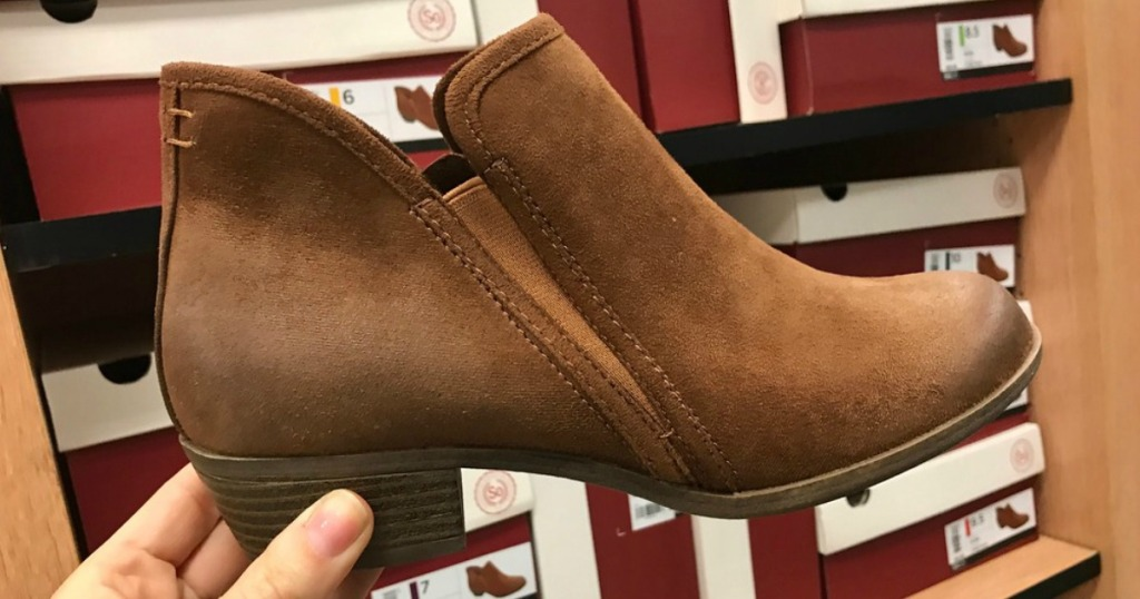 hand holding brown pair of booties in front of shoe boxes