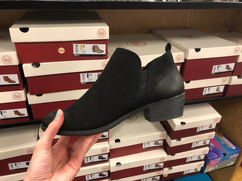 hand holding pair of black booties in front of shoes boxes