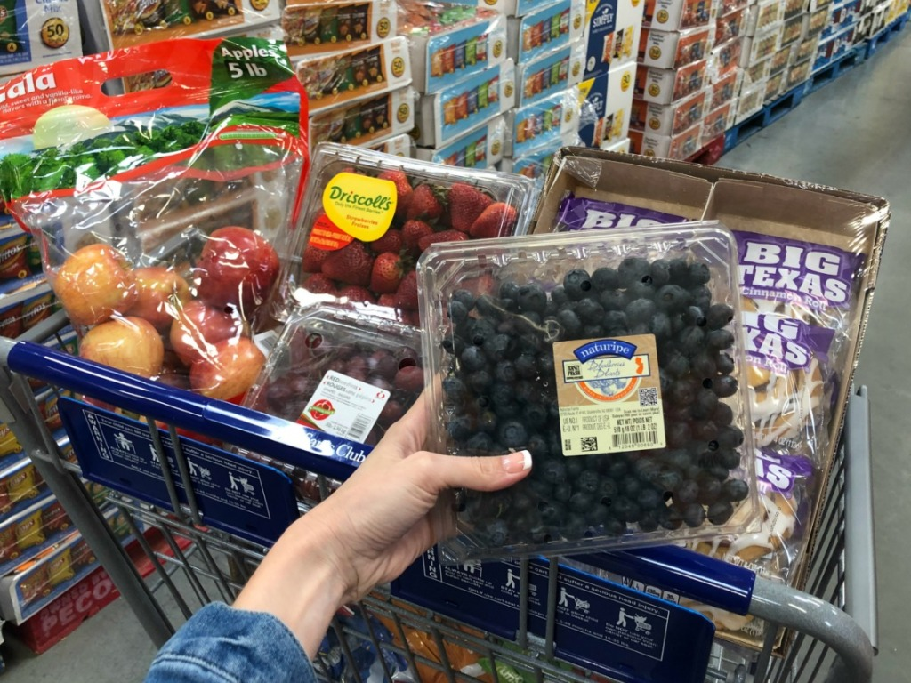 lady holding various grocery items at Sam's club - blueberries and more
