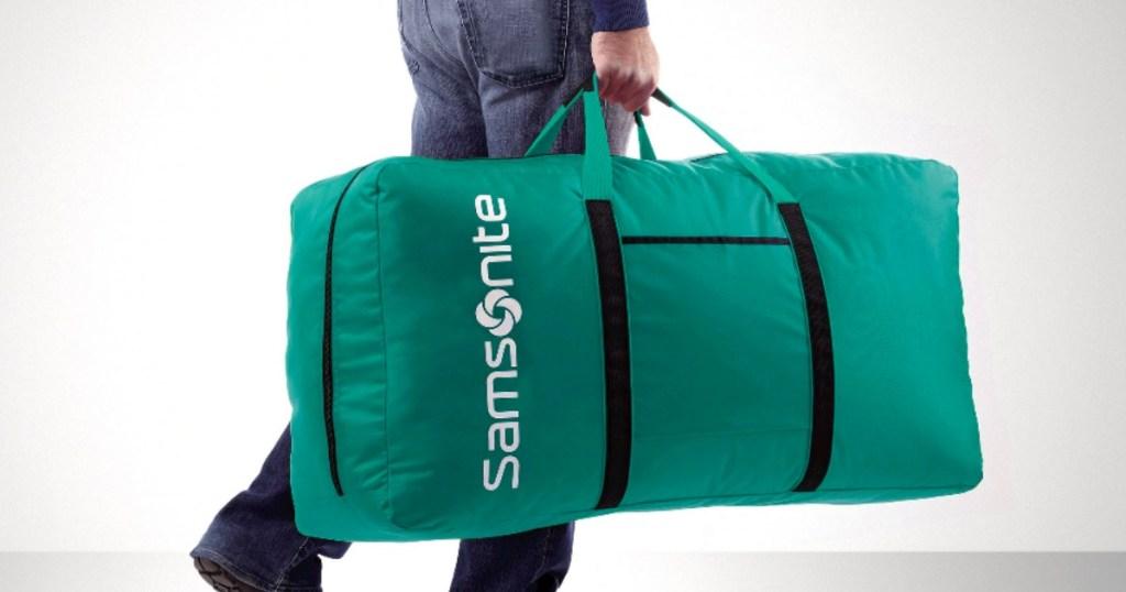 man carrying a Samsonite green Duffle Bag