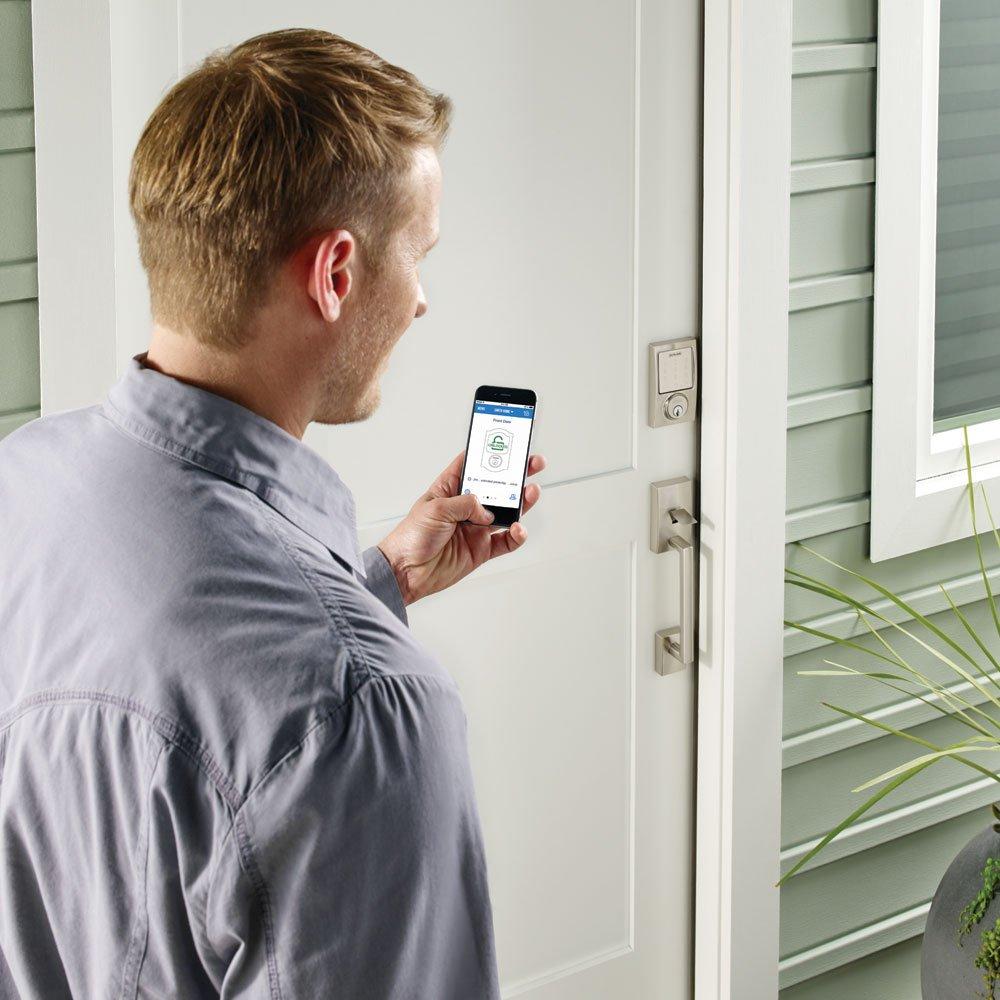 man holding phone to unlock smart lock