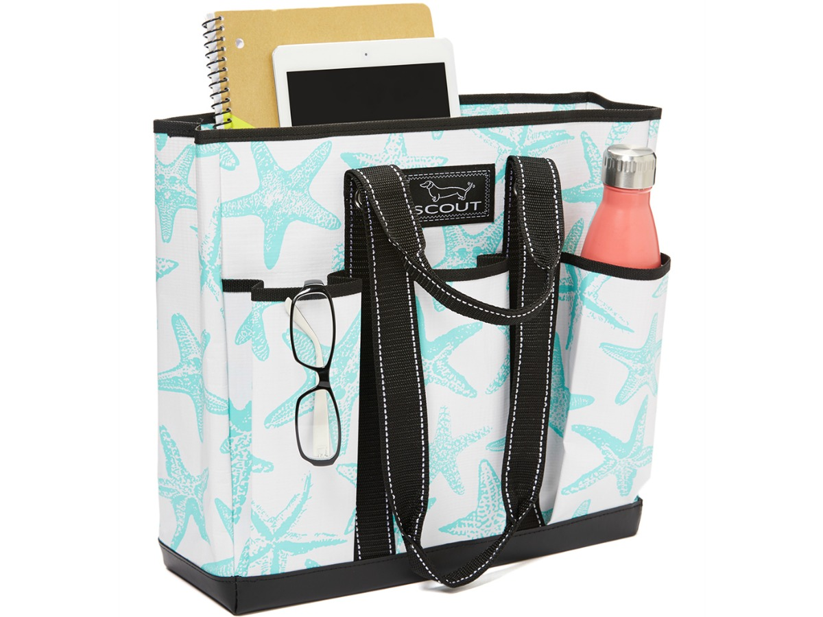 teal and white tote with three front pockets filled with water bottle and other gadgets