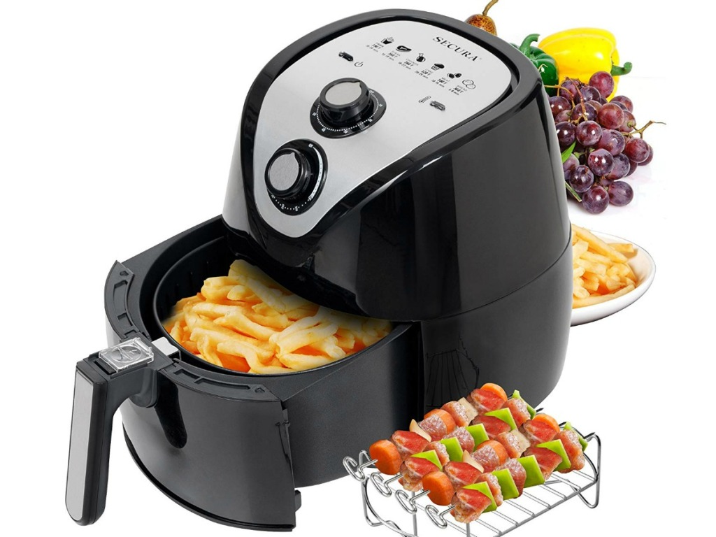 secura air fryer with basket pulled out filled with fries and veggie skewers and fruit beside machine