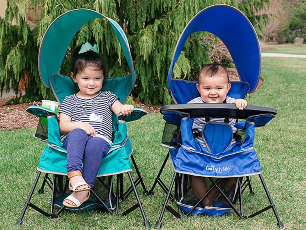 Kids in two portable chairs outside by a tree