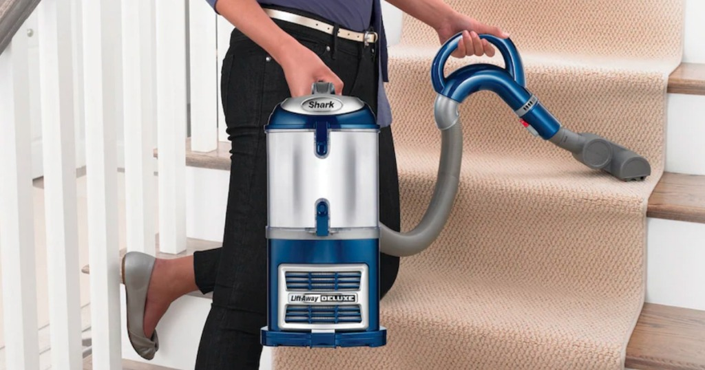 woman using Shark Liftaway Vacuum on stairs